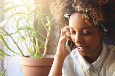女性の肖像若い格好良いアフリカきれいな笑顔の身に着けているバンダナ デニム シャツと彼女のボーイ フレンドの携帯電話で話して座ってインテ