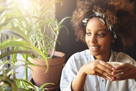 nosering: Portrait of young hipster dark-skinned girl with nose-ring and do-rag on her head, enjoying hot coffee or tea, looking through window with pensive expression, thinking and making plans for day