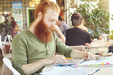 distant work: People, technology and work. Young redhead bearded freelancer with serious and concentrated look using digital tablet for distant work, sitting at coworking cafe, making notes in papers with charts