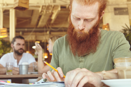 distantly: Young serious freelancer working distantly, using touch pad pc, sitting at cafe, holding pencil and making notes. Redhead student preparing for lesson at university, browsing Internet, looking concentrated