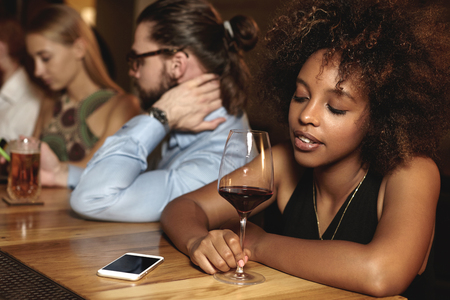 hearted: Sad pensive down hearted dark-skinned woman with glass of red wine at bar counter during New Year celebration, looking at cellphone with copy space for your advertisement, waiting for important call