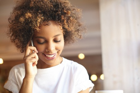 Fashionable good-looking black woman with cute smile and stylish hair, wearing white t-shirt and nose-ring, talking on phone with her friend, smiling, listening to latest news with cheerful expression Фото со стока