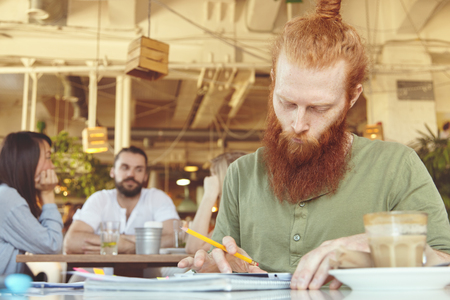 distant work: People and technology. Redhead freelancer with concentrated look using touch pad for distant work, sitting at cafe, holding pencil, analyzing data, making notes, filling in some papers with charts