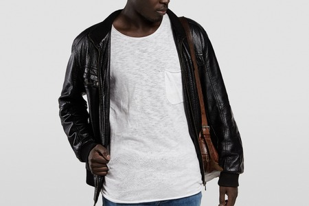 casual wear: Indoor portrait of attractive young African male model dressed casually, posing in studio. Stylish dark-skinned student wearing leather jacket and shoulder bag, getting ready for university Stock Photo
