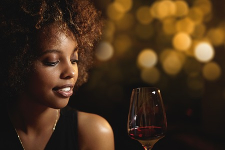 appreciating: Profile of good-looking dark-skinned girl with make-up and Afro hairstyle, holding glass of wine, sitting at bar against blurred lights background with copy space for your text or advertising content