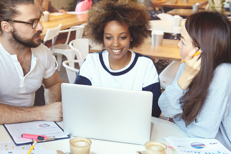 mates: Three students of different ethnic groups at coffee shop chatting with their mates online using laptop while preparing for exams. Business partners working out vision and strategy of their start-up