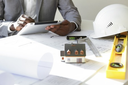 housing project: Cropped shot of dark-skinned contractor holding touch pad, entering data while working on new housing project, sitting at desk with drawings, scale model house, blueprint rolls, ruler and helmets Stock Photo