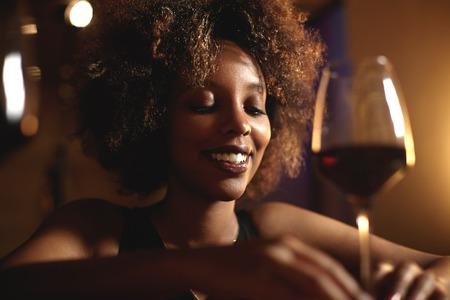 appreciating: Headshot of good-looking young dark-skinned woman with Afro haircut, proposing toast to her friend on birthday party, looking down with shy smile, trying to find right words, holding glass of red wine Stock Photo