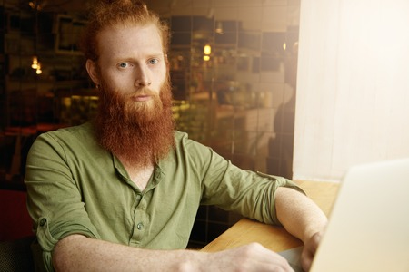 distant work: Young Caucasian freelancer with long red beard dressed casually sitting at coffee shop, using laptop computer for distant work, surfing Internet, looking at camera with serious expression on his face