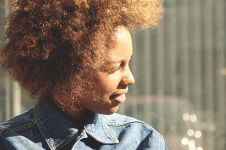nosering: Beautiful African lady with Afro hairstyle and nose-ring, standing outdoors against gray wall with copy space for your text or advertising content, looking aside and squinting her eyes in bright sun