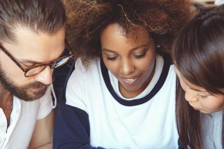 jovenes empresarios: El trabajo en equipo y la cooperación. Tres jóvenes empresarios que trabajan juntos en la cafetería. jefa hermosa que muestra su plan de negocio colegas en la tableta electrónica, inspirado en el nuevo proyecto