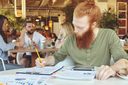 distant work: Hipster freelancer holding pencil, making notes in sheets of paper with graphics, using digital tablet for distant work at co-working space. Redhead student doing home assignment at cafeteria