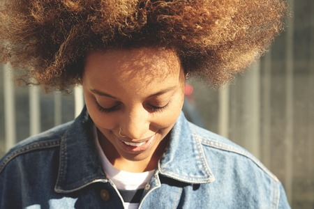 nosering: People and lifestyle. Beautiful African female with healthy skin and nose-ring posing at gray wall, looking down, smiling, showing her white teeth. Black girl with Afro hairstyle relaxing outdoors