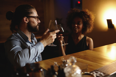 love at first sight: Fashionable interracial couple drinking wine during date, sitting at restaurant, having romantic evening and nice conversation, raising glasses to love at first sight. Hipster man proposing toast Stock Photo