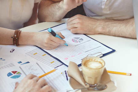 common goals: Startup, goals, growth, success and brainstorming. Creative businesspeople working on common project. Caucasian woman holding felt pen, making analysis of financial data in form of charts and graphics