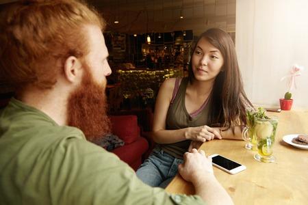 jovenes empresarios: Los jóvenes empresarios que discuten proyecto común que se sienta en la cafetería, pidió un té de menta. Mujer asiática que se refiere mirada, hombre caucásico que toca su móvil con el espacio blanco para su anuncio