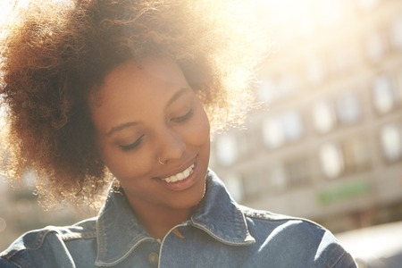 nosering: Attractive happy dark-skinned model with Afro hairstyle and nose-ring, posing outdoors against urban background during her morning walk, looking down with shy smile showing her white teeth. Flare sun Stock Photo