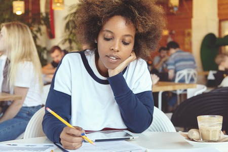 Hipster African female entrepreneur sitting at cafe table with tablet and papers during lunch, working on business plan using touch pad, resting elbow on table, making notes with pencil, looking tired Stock Photo
