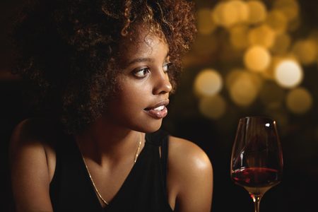 Profile of beautiful African woman with stylish curlly hair wearing elegant black dress, enjoying red wine, siting at restaurant, having romantic dinner with husband, celebrating wedding anniversary Stock Photo