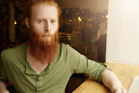 distant work: Portrait of young redhead freelancer dressed casually, looking at camera with serious and thoughtful expression, using wireless Internet connection for distant work, sitting in front of his laptop