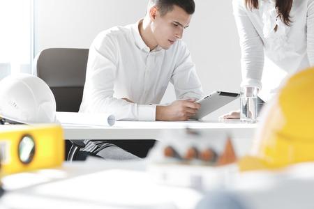 Chefingenieur des Bauunternehmens in seinem Büro sitzt, Touchpad-pc, Projektentwurf mit ernsten Blick zu studieren, während seine Sekretärin am Tisch stehen, um weitere Anweisungen zu warten Standard-Bild