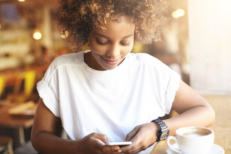 Portrait of fashionable African brunette female with Afro haircut using high-speed Internet connection at cafe, checking her news feed with joyful smile, sitting at cafe with cup of coffee on table 版權商用圖片
