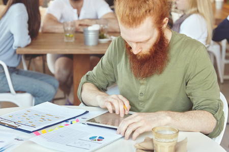 People, technology and work. Young redhead bearded marketing expert using touch pad pc for distant work, sitting alone at cafe table with papers with charts during coffee break, looking serious