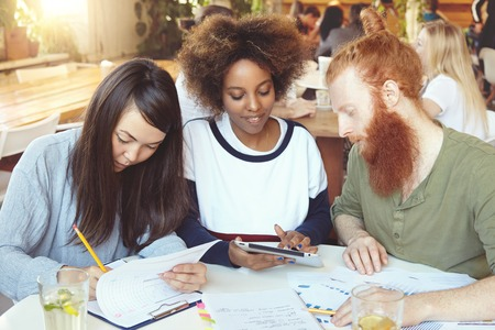 mates: Redhead Caucasian male and his Asian and African female college mates preparing for classes of Economics, sitting at cafe. Dark-skinned student girl showing something to her bearded friend on tablet