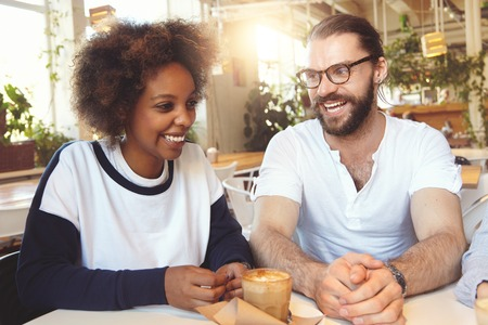 Beautiful interracial couple drinking coffee at cafeteria, handsome bearded Caucasian man in glasses telling something funny to his cute African American girlfriend, both wearing casual clothes 版權商用圖片