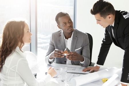 building planners: African boss holding scale model house of future real estate while two young Caucasian engineers presenting their architectural project to him. Group of architects discussing business plans in office Stock Photo