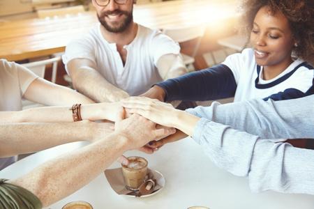 jovenes empresarios: Los socios comerciales de unirse a las manos en círculo. tripulación multiétnica de jóvenes empresarios celebrando el éxito de su proyecto de puesta en marcha, poner las manos en la parte superior de uno al otro que muestra la unidad y la unión Foto de archivo