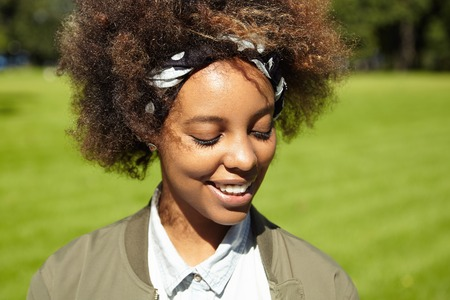 closing time: Outdoor portrait of good-looking young African female with curly hair, having nice time walking in city park. Beautiful girl with charming shy smile, closing her eyes because of bright sunshine
