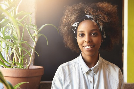 nosering: Portrait of cheerful good-looking fashionable African girl wearing stylish clothes and nose-ring, spending free time at coffee shop, sitting on sofa with aloe plant on background, waiting for friend