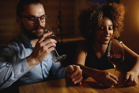 declaring: Side view of mixed race couple in love at restaurant celebrating anniversary, having nice conversation, drinking delicious red wine, remembering good moments, declaring their love to each other again