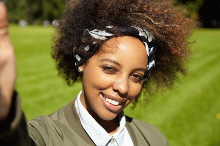 Young stylish woman with Afro haircut wearing black bandana, taking selfie, holding mobile phone or other device in right hand, smiling and squinting eyes in bright sun, standing on green lawn Stock Photo