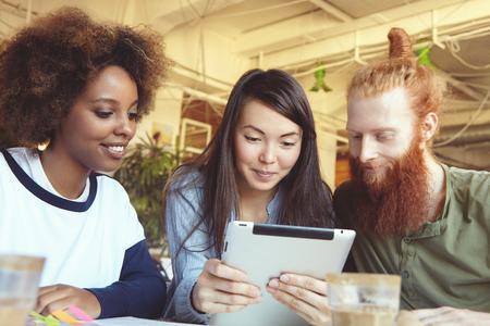 jovenes emprendedores: Equipo, la cooperación y la creatividad. empresarios jóvenes de diversas razas que usa la tableta para el trabajo sobre la estrategia de negocio de su proyecto de inicio, mirando la pantalla con cara feliz expresión inspirada Foto de archivo