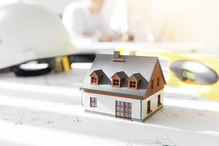 housing project: Design and architecture. Caucasian engineer working on drawings of new housing project, sitting in office with blueprint, ruler, divider compass and tape measure. Selective focus on scale model house Stock Photo