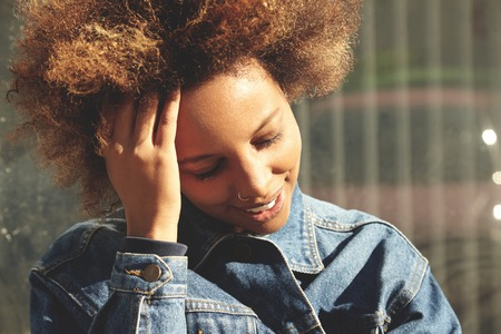 nosering: Flare sun. Portrait of attractive African woman with nose-ring and cute smile, closing her eyes because of bright sun, smiling, touching her hair on windy day while waiting for her friend outdoors