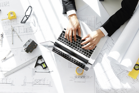 Top view of engineer wearing formal suit working on construction project using laptop, messaging client via email, sitting at office desk with building blueprint, ruler, compass and tape measure