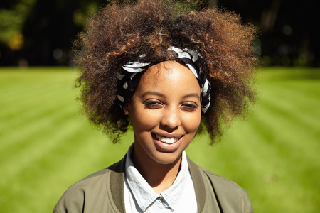 Outdoor portrait of dark-skinned girl on sunny day. Beautiful trendy hipster-looking young female posing against blurred background of green field and forest, squinting her eyes in bright sun Stock Photo