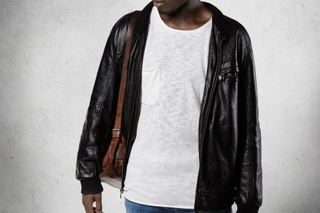 People and fashion. Isolated portrait of stylish young dark-skinned student in trendy clothes, carrying leather bag. Black male model with athletic body posing against studio wall background Stock Photo