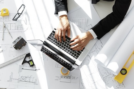 housing project: Top shot of architect or contractor sitting at desk with laptop computer, sketches, scale model house, blueprint rolls and ruler, entering data while working on new housing project in his office Stock Photo