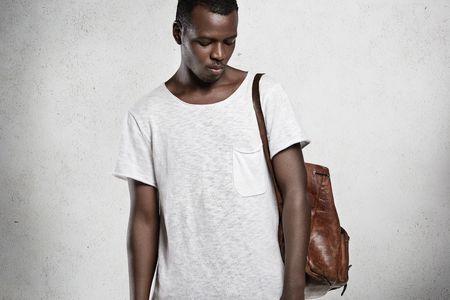 bowing head: Clothing and advertisement concept. Young stylish African male model with athlete body dressed in white copy space t-shirt, bowing his head with closed eyes, posing against concrete wall in studio Stock Photo