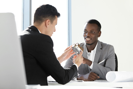 housing project: Teamwork and cooperation. Design and architecture concept. Architect wearing formal suit with scale model house presenting housing project to his African boss sitting at desk with rolls of blueprints