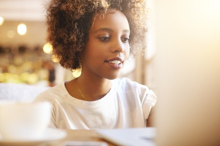 distant work: African female freelancer with Afro hairstyle, dressed casually, using laptop for distant work. Black girl blogger thinking on ideas for her blog, using notebook at co-working space. Selective focus.