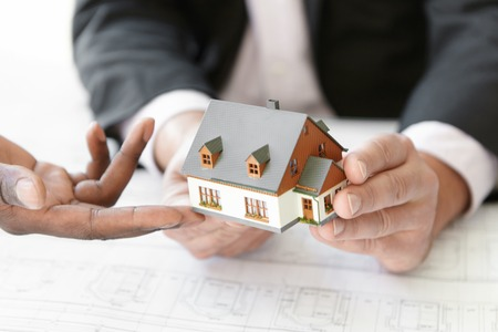 housing project: Architecture, building and construction concept. Cropped shot of two engineers evaluating design of new housing project. African architect making presentation of scale model house to his partner
