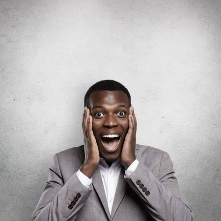 Amazed young African businessman dressed in formal wear, looking excited and shocked, holding hands on cheeks, screaming with mouth wide open, astonished with profitable business offer or big sale