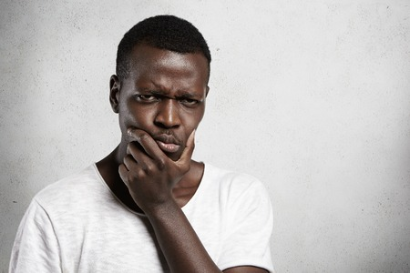 skepticism: Portrait of skeptical African young man looking with suspicious or annoyed expression, holding hand on chin, doubting, thinking over something. Black male with disgust or disapproval on his face Stock Photo