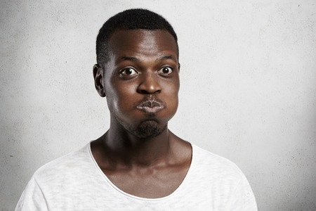 clowning: Headshot of bug-eyed young African man grimacing, inflating his cheeks, holding his breath, trying hard not to laugh, looking at camera with funny face expression, clowning and having fun indoors Stock Photo