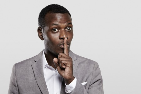 concealing: Dark-skinned entrepreneur in gray suit holding finger on his lips, asking to keep confidential information private, concealing commercial secret, saying hush. Black boss asking employees to be quiet